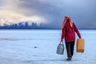 A local woman getting fresh water from the frozen lake of Tsagaan Nuur, Northern Mongolia
